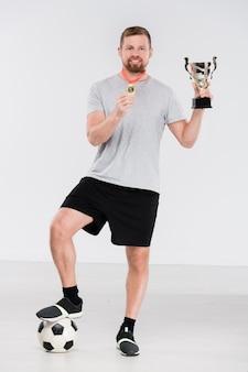Junger erfolgreicher fußballspieler in der sportbekleidung, die silberpokal und goldmedaille zeigt, während er isoliert vor der kamera steht