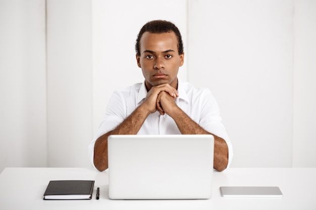 Junger erfolgreicher geschäftsmann, der am arbeitsplatz mit laptop sitzt