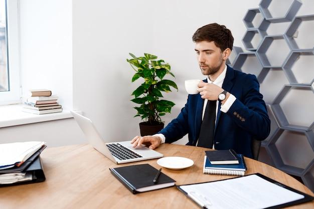 Junger erfolgreicher geschäftsmann, der am laptop, bürohintergrund sitzt.
