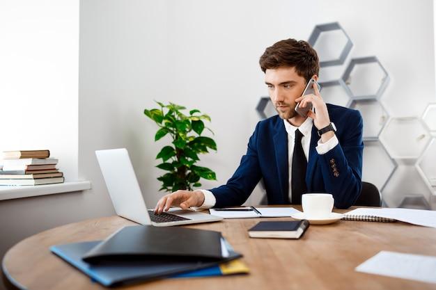 Junger erfolgreicher geschäftsmann, der am telefon, bürohintergrund spricht.