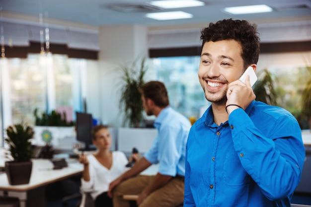 Junger erfolgreicher geschäftsmann, der am telefon, lächelnd, über büro spricht