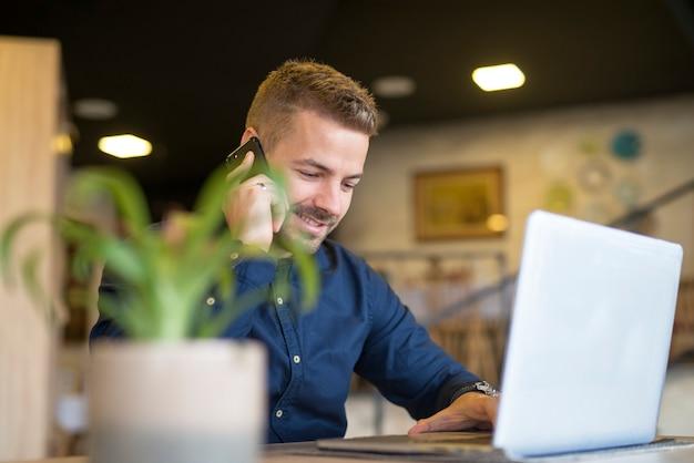 Junger erfolgreicher geschäftsmann, der am telefon spricht und laptop im café-bar-restaurant verwendet