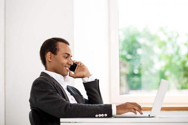 Junger erfolgreicher geschäftsmann, der am telefon spricht und laptop schreibt