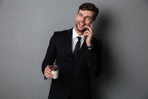 Junger erfolgreicher geschäftsmann, der auf handy spricht, während tasse kaffee hält, beiseite schaut