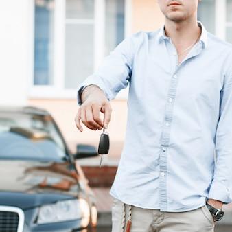 Junger erfolgreicher geschäftsmann, der einen autoschlüssel anbietet