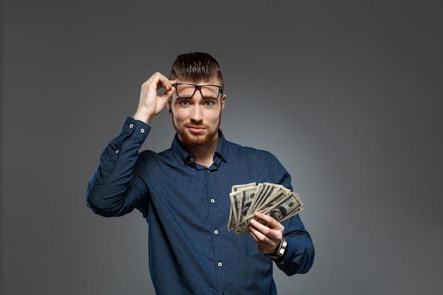 Junger erfolgreicher geschäftsmann, der geld über dunkler wand hält.