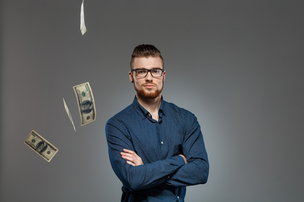 Junger erfolgreicher geschäftsmann, der unter fallendem geld über dunkler wand aufwirft.
