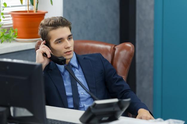 Junger erfolgreicher geschäftsmann im anzug sitzt mit computer am arbeitsplatz am tisch und telefoniert