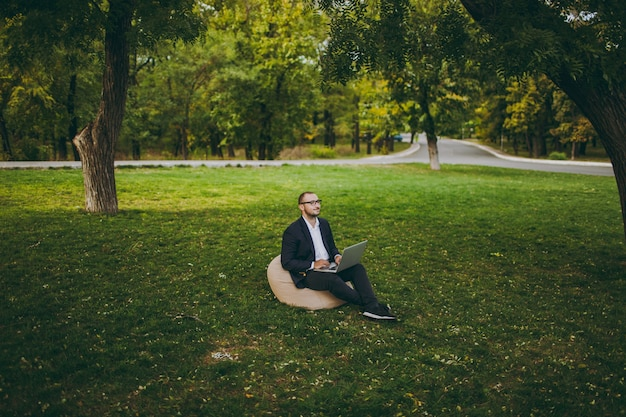 Junger erfolgreicher geschäftsmann im weißen hemd, im klassischen anzug, in der brille. der mann sitzt auf einem weichen hocker und arbeitet an einem laptop-pc im stadtpark auf grünem rasen im freien in der natur. mobiles büro, geschäftskonzept.