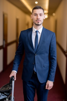 Junger erfolgreicher geschäftsmann in der abendgarderobe, der im langen korridor des hotels steht, während er in sein zimmer zieht