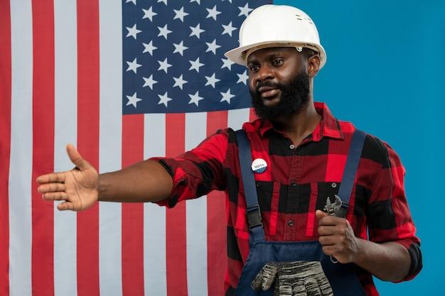 Junger erfolgreicher handwerker oder erbauer afrikanischer ethnizität, der dem kollegen seine hand zum händedruck mit amerikanischer flagge gibt