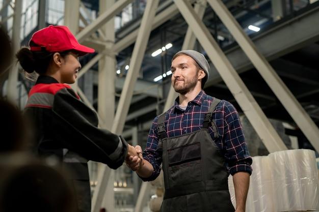 Junger erfolgreicher ingenieur in overalls und kariertem hemd, der seiner kollegin in uniform während der teamarbeit im lager die hand schüttelt