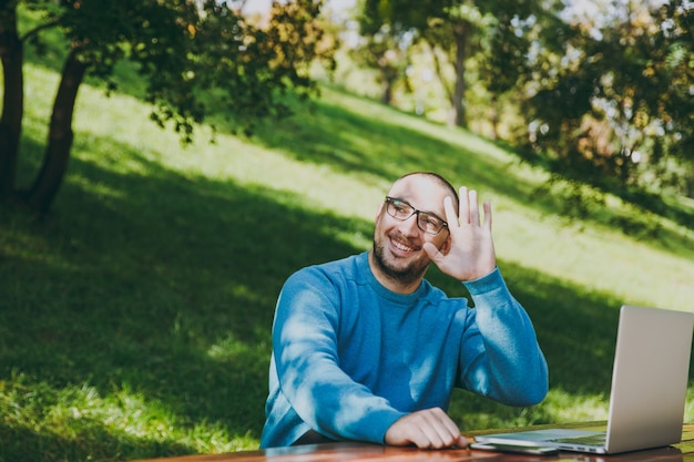 Junger erfolgreicher intelligenter geschäftsmann oder student in lässigem blauem hemd, brille am tisch sitzend mit handy im stadtpark mit laptop, der im freien arbeitet, zeigen hallo-geste. mobile office-konzept.