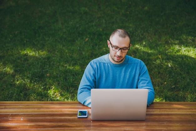 Junger erfolgreicher intelligenter geschäftsmann oder student in lässiger blauer hemdbrille, der am tisch mit handy im stadtpark sitzt und laptop verwendet, der draußen auf grünem hintergrund arbeitet. mobile office-konzept.