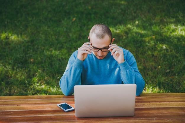 Junger erfolgreicher intelligenter geschäftsmann oder student in lässiger blauer hemdbrille, der am tisch mit handy im stadtpark sitzt und laptop verwendet, der draußen auf grüner natur arbeitet. mobile office-konzept.