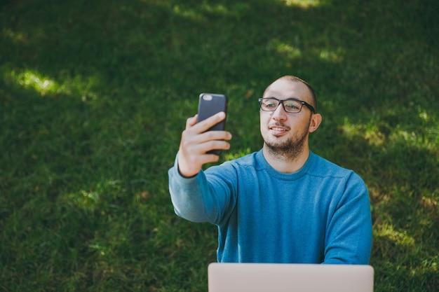 Junger erfolgreicher intelligenter lustiger geschäftsmann oder student in lässigem blauem hemd, brille sitzt am tisch und macht selfie auf dem handy im stadtpark mit laptop, arbeitet im freien. mobile office-konzept.