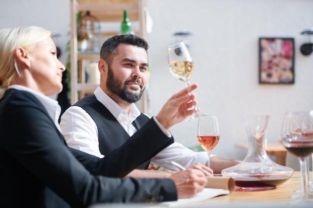 Junger erfolgreicher kavist, der weißwein betrachtet, der von seinem kollegen während der prüfung seiner eigenschaften gehalten wird
