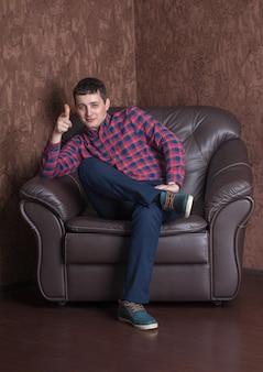 Junger erfolgreicher kerl, der auf einem ledersessel sitzt.