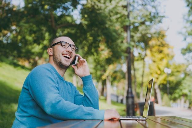 Junger erfolgreicher lächelnder intelligenter manngeschäftsmann oder -student in lässigem blauem hemd, brille sitzt am tisch, telefoniert im stadtpark mit laptop, arbeitet im freien. mobile office-konzept.