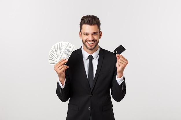 Junger erfolgreicher schöner reicher geschäftsmann im schwarzen anzug, der banknote und kreditkarte lokalisiert auf weißer wand für werbung hält.