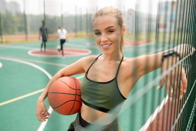 Junger erfolgreicher weiblicher basketballspieler mit ball, der sie beim stehenbleiben auf netzspielplatz im freien betrachtet