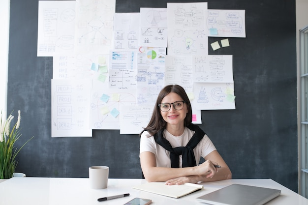 Junger erfolgreicher weiblicher ökonom, der durch schreibtisch auf hintergrund der tafel mit papieren und arbeiten sitzt