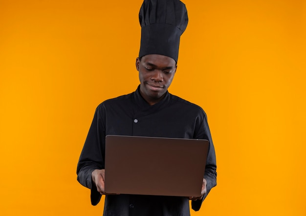Junger erfreuter afroamerikanischer koch in der kochuniform hält und schaut auf notizbuch auf orange mit kopienraum