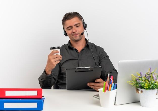Junger erfreuter blonder büroangestellter mann auf kopfhörern sitzt am schreibtisch mit bürowerkzeugen unter verwendung des laptop hält zwischenablage und kaffeetasse lokalisiert auf weißem hintergrund mit kopienraum