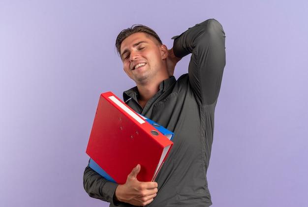 Junger erfreuter blonder hübscher mann hält aktenordner und legt hand auf hals hinter isoliert auf violettem raum mit kopierraum