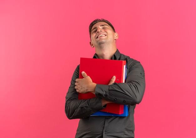 Junger erfreuter blonder hübscher mann hält dateiordner lokalisiert auf rosa hintergrund mit kopienraum