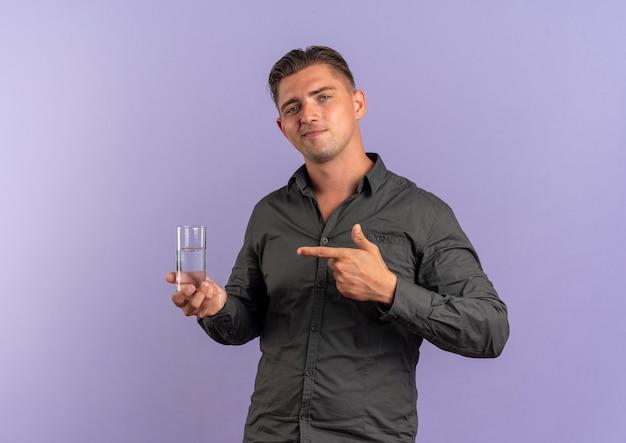 Junger erfreuter blonder hübscher mann hält und zeigt auf glas wasser, das auf violettem raum mit kopierraum isoliert ist