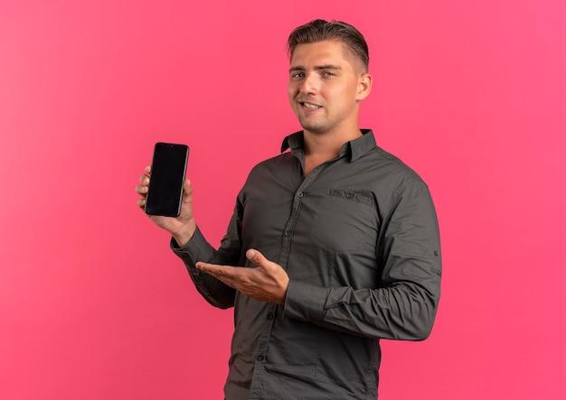Junger erfreuter blonder hübscher mann hält und zeigt auf telefon lokalisiert auf rosa hintergrund mit kopienraum