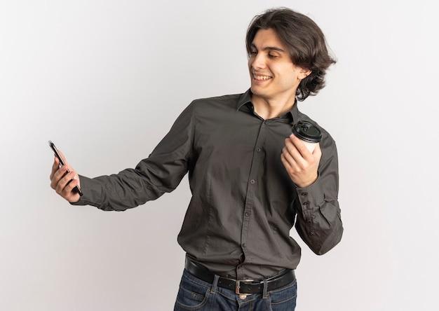 Junger erfreuter hübscher kaukasischer mann hält telefon und kaffeetasse, die telefon lokalisiert auf weißem hintergrund mit kopienraum betrachten