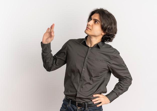 Junger erfreuter hübscher kaukasischer mann schaut zur seite und gestikuliert ok handzeichen lokalisiert auf weißem hintergrund mit kopienraum