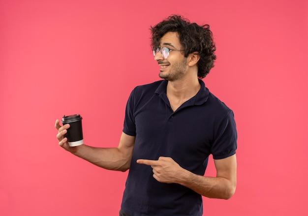 Junger erfreuter mann im schwarzen hemd mit optischen gläsern hält und zeigt auf kaffeetasse, die seite betrachtet, die auf rosa wand lokalisiert wird