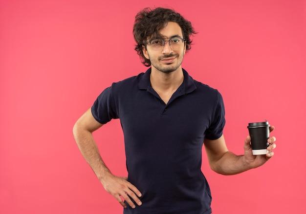 Junger erfreuter mann im schwarzen hemd mit optischer brille hält kaffee zum mitnehmen tasse und legt hand auf taille isoliert auf rosa wand
