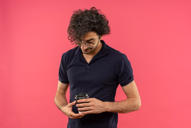Junger erfreuter mann im schwarzen hemd mit optischer brille hält und betrachtet tasse kaffee lokalisiert auf rosa wand
