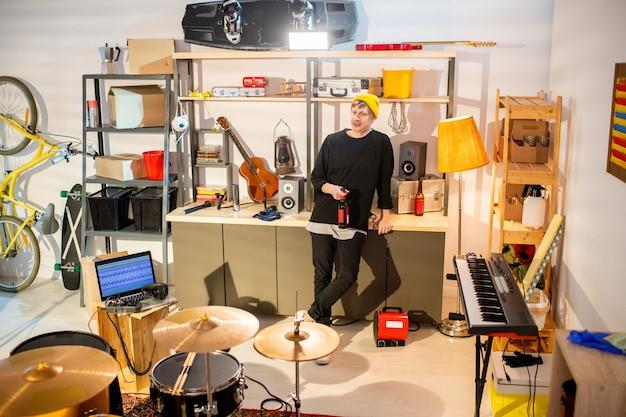 Junger erholsamer musiker in freizeitkleidung mit einer flasche bier beim stehen am tisch mit musikinstrumenten und haushaltsgegenständen in der garage