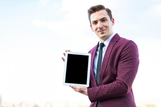 Junger ernster geschäftsmann im roten anzug und hemd mit bindung stehen auf dem dach mit leerer tablette