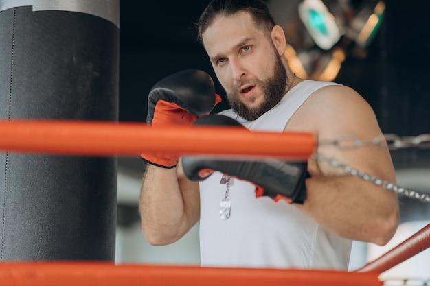 Junger ernster mann, der auf boxring hemdlos steht und fokussiert der kamera betrachtet