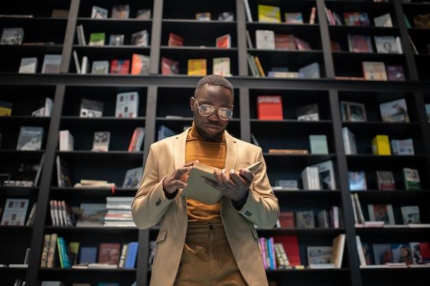 Junger ernster mann in intelligenter freizeitkleidung und brillenlesebuch gegen bücherregale