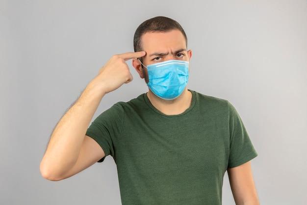 Junger ernsthaft aussehender mann, der medizinische gesichtsmaske trägt, die auf seinen kopf mit dem auf weiß lokalisierten finger zeigt