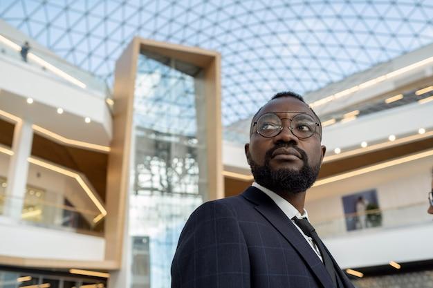 Junger ernsthafter afrikanischer geschäftsmann, der sich gegen moderne architektur freut