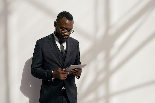 Junger ernsthafter afroamerikanischer broker mit tablet, der finanznachrichten durchschaut