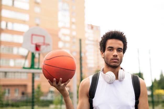 Junger ernsthafter aktiver männlicher korbballer im weißen t-shirt, das ball hält, während auf spielplatz steht