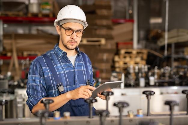 Junger ernsthafter angestellter der industrieanlage, der im touchpad scrollt, während er neue technische ausrüstung im arbeitsbereich testet