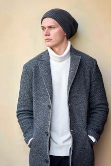 Junger ernsthafter attraktiver hipster-trendmann, der einen grauen mantel, einen weißen pullover und schwarze jeans trägt. porträt. draußen.
