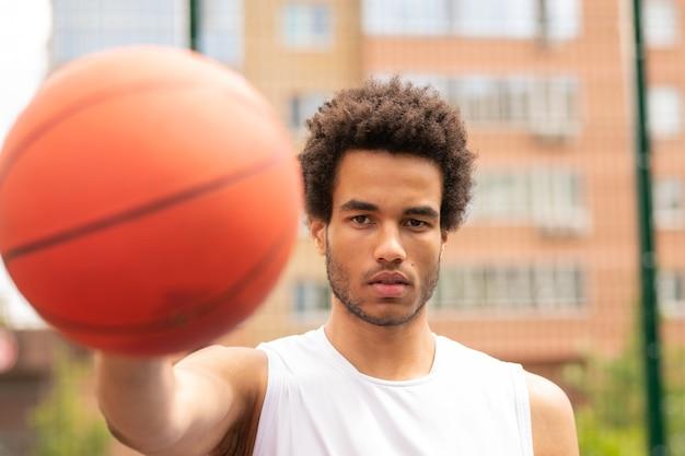 Junger ernsthafter basketballspieler, der sie beim passieren des balls oder beim werfen in den korb ansieht
