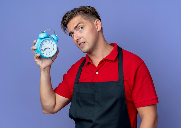 Junger ernsthafter blonder männlicher friseur in der uniform hält wecker isoliert auf violettem raum mit kopienraum