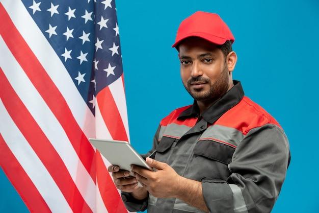 Junger ernsthafter fabrikarbeiter mittleren alters oder handwerker in arbeitskleidung mit touchpad beim stehen gegen sternenbanner auf blau